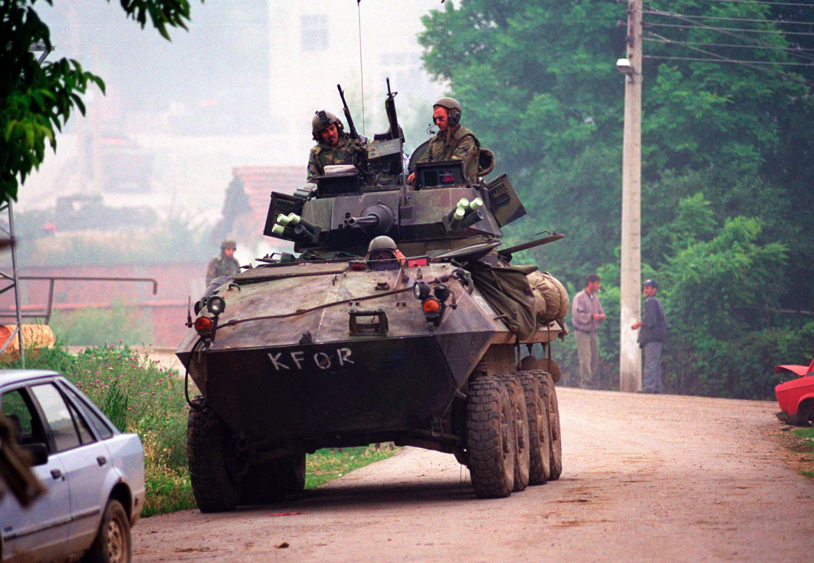 990627-M-5696S-011 	A U.S. Marine Corps Light Armored Vehicle (LAV-25) from the 2nd Light Armored Reconnaissance Battalion patrols in the village of Zegra, Kosovo, on June 27, 1999.  Elements of the 26th Marine Expeditionary Unit are deployed from ships of the USS Kearsarge Amphibious Ready Group as an enabling force for KFOR.  KFOR is the NATO-led, international military force which will deploy into Kosovo on a peacekeeping mission known as Operation Joint Guardian.  KFOR will ultimately consist of over 50,000 troops from more than 24 contributing nations, including NATO member-states, Partnership for Peace nations and others.  DoD photo by Sgt. Craig J. Shell, U.S. Marine Corps.  (Released)